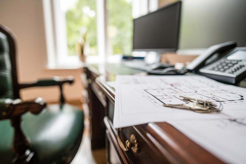 Schreibtisch mit Grundrissen und Schlüssel